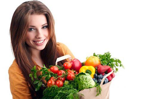 Девушка держит овощи и фрукты