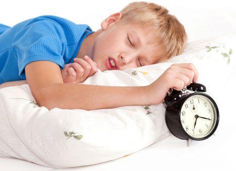 Рука спящего ребенка на будильнике